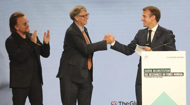 Emmanuel Macron, right, with Bill Gates, centre, and U2 singer Bono at the Global Fund event in Lyon (Laurent Cipriani/AP)