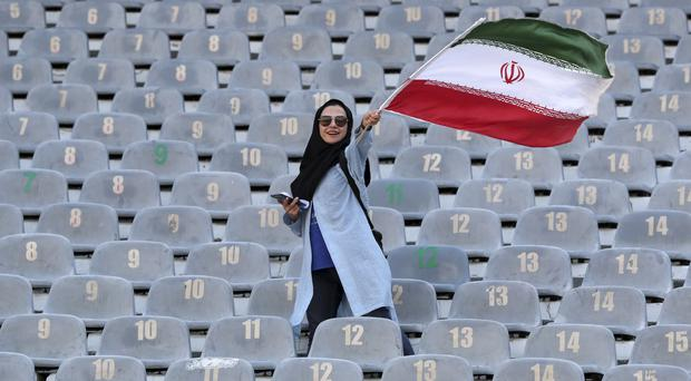An Iranian woman waves her country's flag as she arrives at the Azadi Stadium in Tehran (Vahid Salemi/AP)