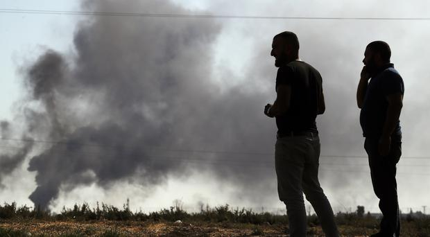 People in Akcakale Sanliurfa province, southeastern Turkey, at the border with Syria, watch smoke billowing from targets inside Syria (Lefteris Pitarakis/AP)