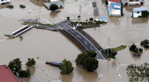Cars stranded on a road as the city is submerged in muddy waters after an embankment of the Chikuma River broke, in Nagano, Japan (Yohei Kanasashi/AP)