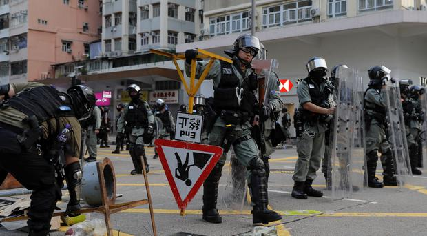 Riot police remove barricade made by protesters (Kin Cheung/AP)