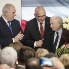 Leader of Poland's ruling party Jaroslaw Kaczynski, right, and party activists react to exit poll results (STR/PA)
