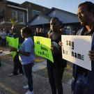 Protesters gather outside the house (Smiley N. Pool/The Dallas Morning News via AP)