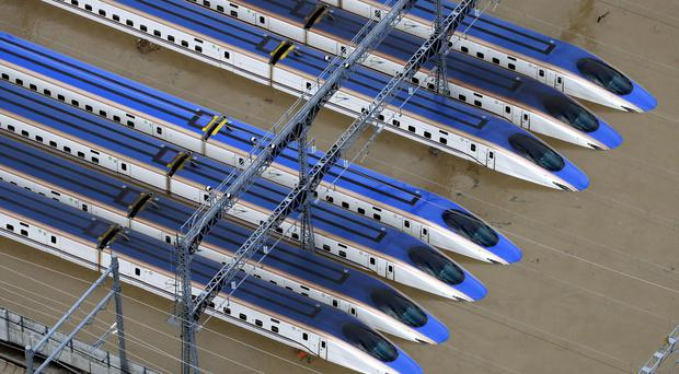 Bullet trains are seen submerged in muddy waters in Nagano (Yohei Kanasashi/AP)