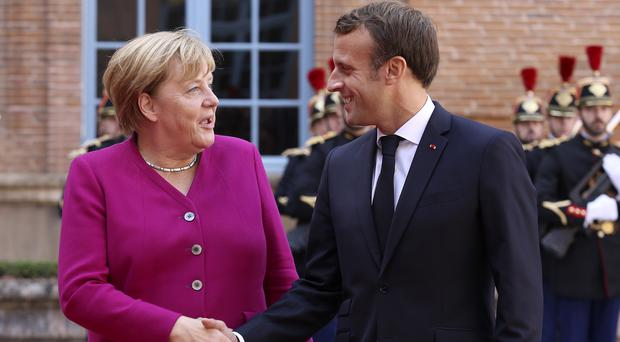 French president Emmanuel Macron welcomes German chancellor Angela Merkel in the government building of Toulouse (Frederic Scheiber/AP)