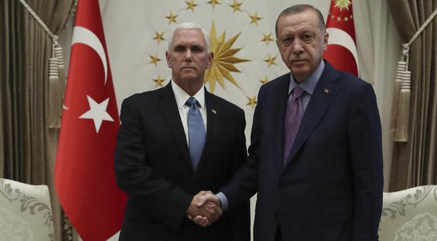 Turkey's President Recep Tayyip Erdogan, right, shakes hands with US vice president Mike Pence (Presidential Press Service via AP, Pool)