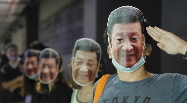 Protesters wear masks of Chinese president Xi Jinping (AP)