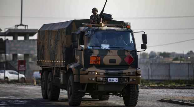 Turkish soldiers on a truck drive back from Syria, in the border town of Akcakale, Sanliurfa province (Emrah Gurel/AP)