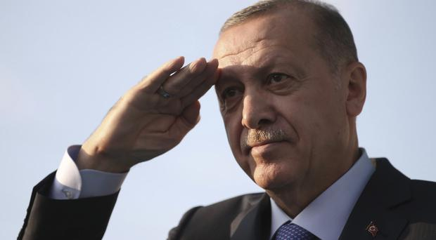 Turkish President Recep Tayyip Erdogan gives a military-style salute towards his supporters during a rally in Kayseri, Turkey (Presidential Press Service/AP)