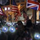 Protesters flash their smartphone lights and wave British and American flags at a prayer rally in Hong Kong on Saturday night (Mark Schiefelbein/AP)