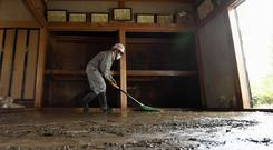 A volunteer continues to clean up mud from last week's Typhoon Hagibis, in Nagano (Keisuke Koito/Kyodo News via AP/PA)