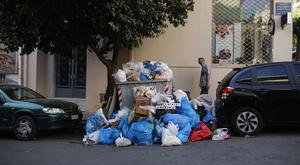 A man looks at a pile of rubbish in the central Koukaki area of Athens (Petros Giannakouris/AP/PA)