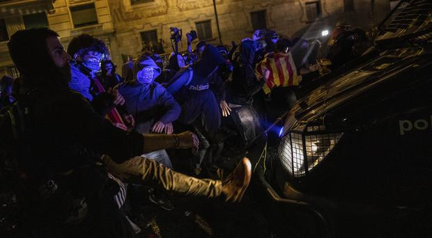 Protesters kick a police van during clashes in Barcelona (AP)