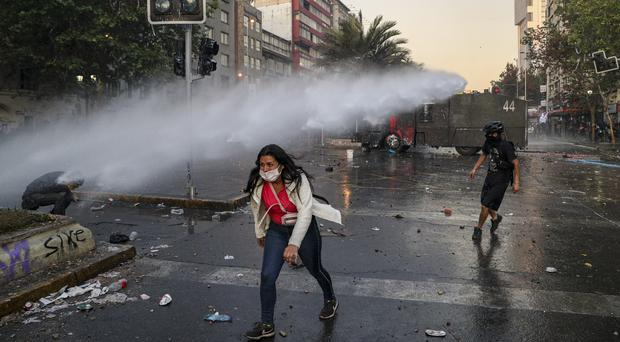 An anti-government protester walks away from the spray of a police water cannon in Santiago, Chile (Esteban Felix/AP)