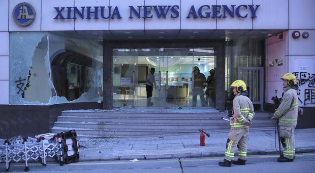 Firefighters outside the offices of China's Xinhua News Agency in Hong Kong (Kin Cheung/AP)