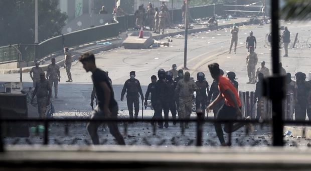 Iraqi riot police fire tear gas to disperse anti-government protesters gathering on a bridge in central Baghdad (Hadi Mizban/AP)