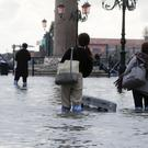 Tourists push their luggage in a flooded St Mark's Square in Venice (Luca Bruno/AP)