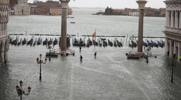 People make their way in a flooded St Mark's Square in Venice (Luca Bruno/AP)