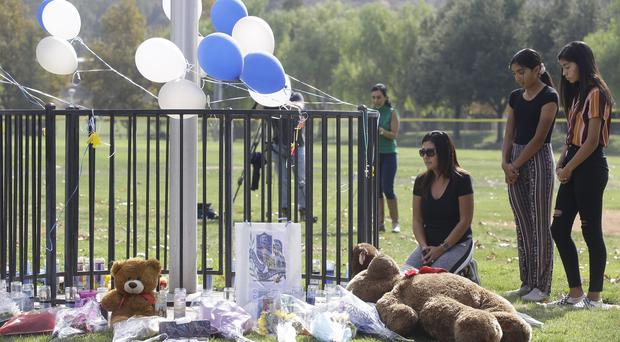 Parent Mirna Herrera kneels with her daughters Liliana, 15, and Alexandra, 16 at the Central Park memorial for the Saugus High School victims (Damian Dovarganes/AP/PA)