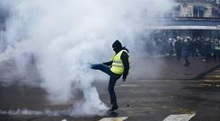 A protestor kicks away a tear gas canister during a yellow vest demonstration in Paris (Kamil Zihnioglu/AP/PA)