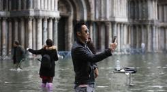 Tourists take pictures in a flooded St. Mark's Square, in Venice on Friday(Luca Bruno/AP/PA)