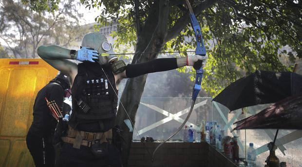 A protestor prepares to fire a bow and arrow in Hong Kong (AP/Kin Cheung)