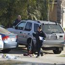 Fresno police investigators work near the driveway where a shooting took place (Gary Kazanjian/AP/PA)