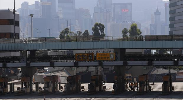 Workers inspect the damage from protesters on the toll booths of the Cross-Harbour Tunnel near the Polytechnic University in Hong Kong (Vincent Thian/AP)