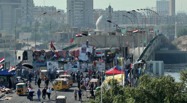 Protesters stage a sit-in at barriers on the Sinak Bridge in Baghdad (Hadi Mizban/AP)