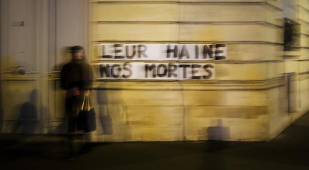 A slogan reading 'Their hate, our dead' has been painted on a wall in Paris by anti-domestic violence campaigners (Kamil Zihnioglu/AP)