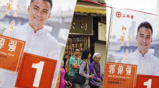 People walk past campaign banners outside a polling station (Vincent Yu/AP)