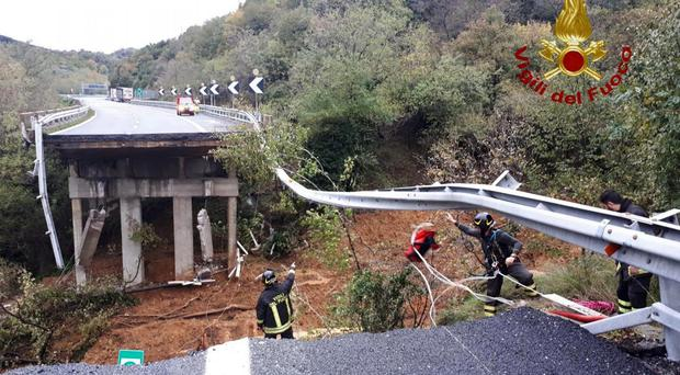 Firefighters work in the area where a stretch of the Turin to Savona A6 road collapsed (Vigili del Fuoco/AP)