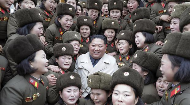 North Korean leader Kim Jong Un, centre, poses as he inspects a women's company (Korean Central News Agency/AP)