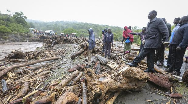 Passengers from stranded vehicles stand next to the debris from floodwaters, in Kenya (AP)
