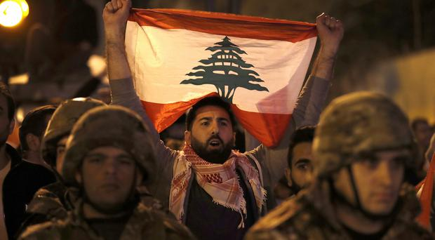 An anti-government protester holds his nation's flag as he stands behind Lebanese army soldiers during a clash between the anti-government protesters and the supporters of the Shiite Hezbollah and Amal Movement groups, in Beirut (Hussein Malla/AP)