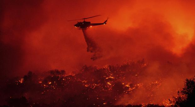 A helicopter drops water on the fire in Los Padres National Forest, California, above Santa Barbara (Noah Berger/AP)