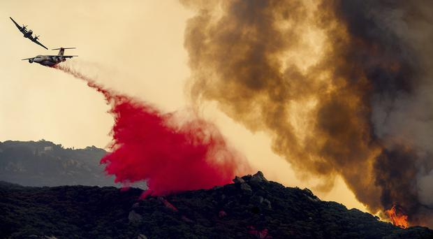 An air tanker drops retardant to slow the burning in Los Padres National Forest (Noah Berger/AP)