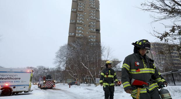 Minneapolis firefighters leave after a deadly fire at a high-rise apartment building (Star Tribune/AP)