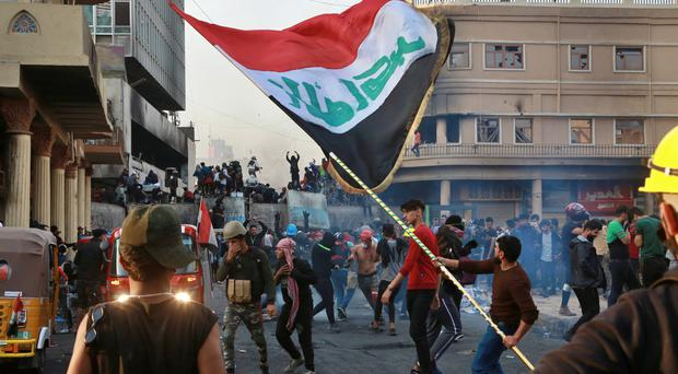 Anti-government protesters gather during clashes with security forces in Baghdad (Khalid Mohammed/AP)