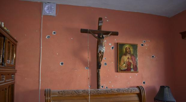A wall is riddled with bullet holes after a gun battle between Mexican security forces and suspected cartel gunmen (Gerardo Sanchez/AP)