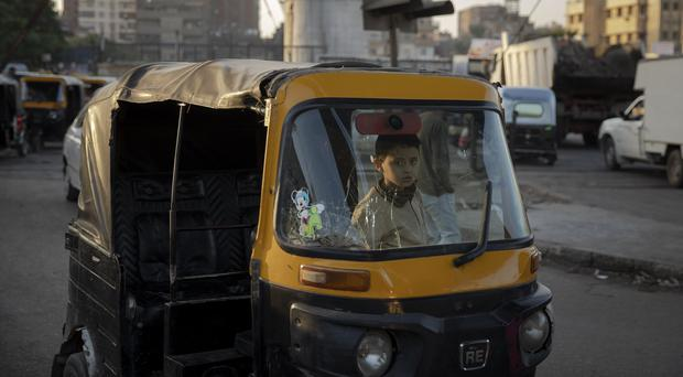 A boy sits in the driver's seat of a tuk-tuk in a slum in Cairo, Egypt (Nariman El-Mofty/AP)