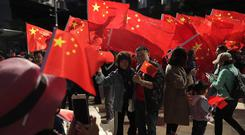 Pro-Beijing supporters wave Chinese national flags during a rally in Hong Kong (Mark Schiefelbein/AP)