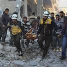 An injured person is removed from the remains of a building hit in the air strikes (Syrian Civil Defence White Helmets via AP)
