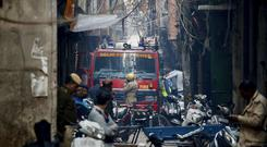 A fire engine stands by the site of a fire in a narrow lane in New Delhi (Manish Swarup/AP)