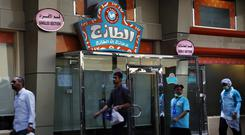 People walk in front of a restaurant with signs at top left reads 'single section' and at top right reads, 'family section' (AP/Amr Nabil)