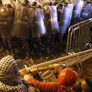 Anti-government protesters remove the fences dividing them from riot police (AP/Hussein Malla)