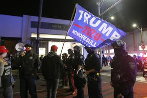 Police officers stand in front of Trump supporters marching in Beverly Hills, California (Ringo HW Chiu/AP)