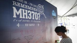 A girl writes a condolence message during the Day of Remembrance for MH370 (Vincent Thian/AP)