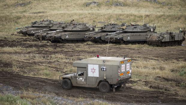 An Israeli military ambulance drives past tanks in the Israeli-controlled Golan Heights, near the border with Syria (Ariel Schalit/AP)