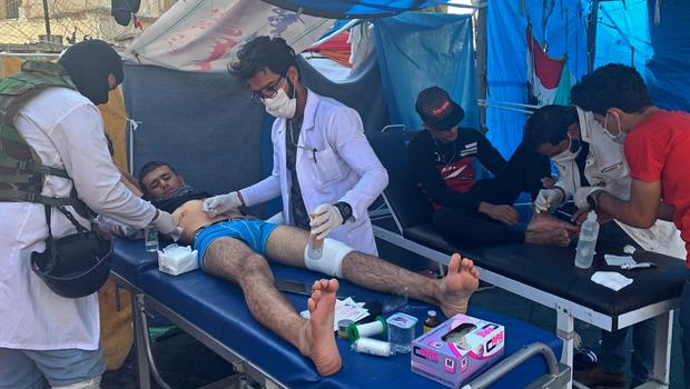 Protesters receive treatment at Tahrir Square in Baghdad after renewed clashes with security forces (Ali Abdul Hassan/AP)